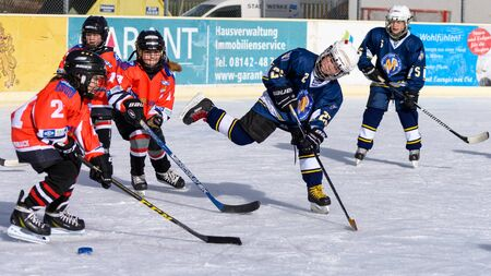 about age: Fuerstenfeldbruck, Bavaria, Germany - 06. February 2016: German Kids playing ice hockey. Age is about 10 years. Orange Players trie a defense, but blue player goes through and shoots to the goal.