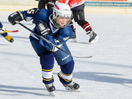 about age: Fuerstenfeldbruck, Bavaria, Germany - 06. February 2016: German Kids playing ice hockey. Age is about 10 years. Close up of a single blue player in action.