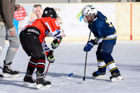about age: Fuerstenfeldbruck, Bavaria, Germany - 06. February 2016: German Kids playing ice hockey. Age is about 10 years. Kick-off fight for the puck.