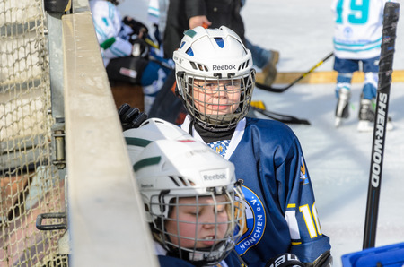 age 10: Fuerstenfeldbruck, Bavaria, Germany - 06. February 2016: German Kids playing ice hockey. Age is about 10 years. Players resting on the bench.
