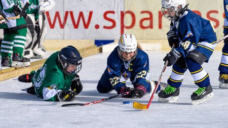 racket stadium: Fuerstenfeldbruck, Bavaria, Germany - 06. February 2016: German Kids playing ice hockey. Age is about 10 years. Players went to the ground, but are still fighting for the puck.