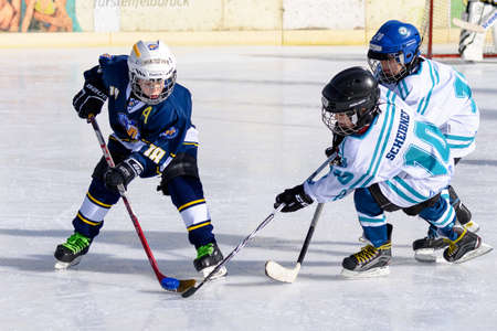 about age: Fuerstenfeldbruck, Bavaria, Germany - 06. February 2016: German Kids playing ice hockey. Age is about 10 years. Single blue player maneuvering through heavy defense. Editorial