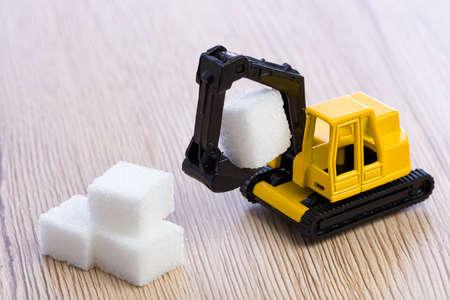 grabbing: Small, yellow toy excavator grabbing a piece of sugar. Stock Photo