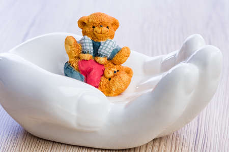 unconcerned: Two little bear children carelessly playing while protected in a white hand.