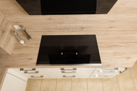 electric stove: Top down view on modern induction ceramic hob with extractor hood above.