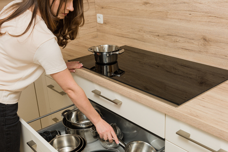 Workflow in a modern kitchen: woman working in front of touch panel cooker with open drawer under the stove.