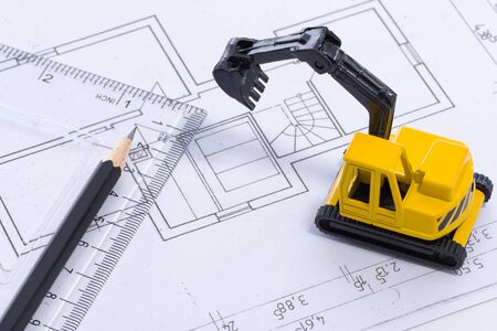 constructional: Desktop with blueprint yellow mini excavator, ruler and pencil symbolizing the wish to build own home