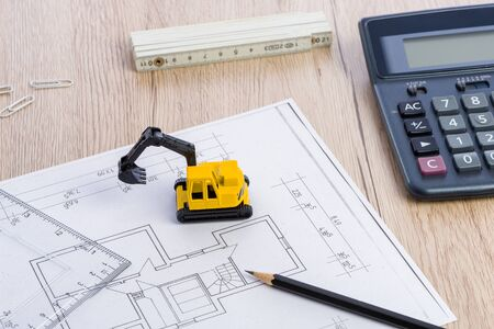 Desktop with blueprint yellow mini excavator, ruler, pencil and calculator symbolizing the wish to build own home