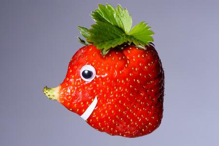 pez globo: Fresa con la nariz crecida natural como una cara. Tiene una forma �nica y se parece a un pez globo, elefante o lunar. Foto de archivo