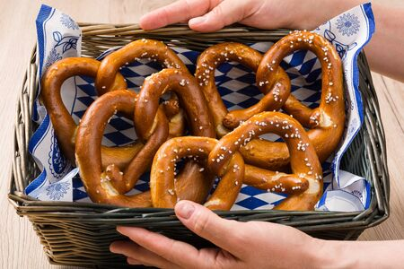 breadbasket: Breadbasket with traditional Bavarian pretzels served by two hands. Stock Photo