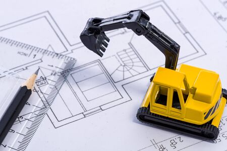 Desktop with blueprint yellow mini excavator, ruler and pencil symbolizing the wish to build own home