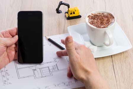 Close-up of architect hands working on a blueprint and holding a smartphone. Cup of coffee and miniature extractor in the background. Blueprint was created by photographer.