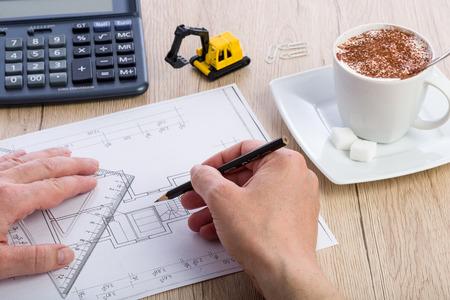 Close-up van architectenhanden die aan een blauwdruk werken. Rekenmachine, kopje koffie en miniatuur extractor op de achtergrond. Blueprint is gemaakt door fotograaf.