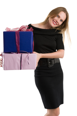Attractive blonde woman in elegant black dress carrying big gift packages, isolated on white