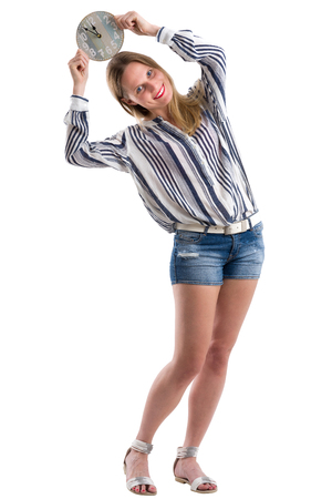 Smiling blonde woman playing with a clock and showing the time, isolated on white