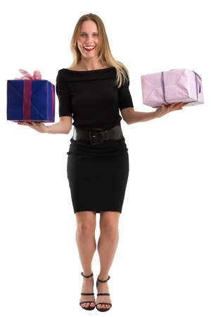 Attractive blonde woman in elegant black dress juggling big gift packages, isolated on white