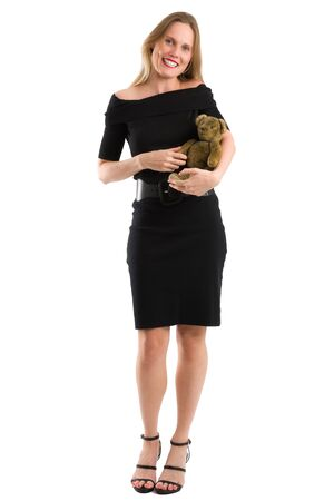 Attractive blonde woman in elegant black dress canoodling her antique teddy, isolated on white