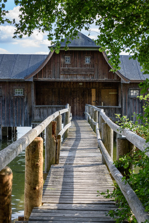 Footbridge leading to old wooden boats house on German lake. Stock Photo