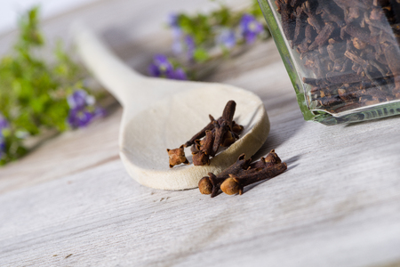 Group of dried cloves poured with spoon on wooden cutting board. Stock Photo