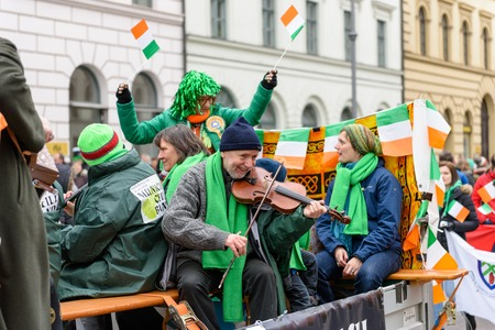 MUNICH, BAVARIA, GERMANY - MARCH 13, 2016: waggon with cheering Irish people and a man playing skillfully his violin at the St. Patrick's Day Parade.
