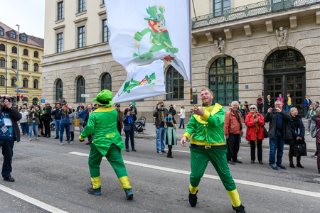 MUNICH, BAVARIA, GERMANY -  MARCH 11, 2018: group of flag wavers masked with red beard and green hat at the St. Patrick's Day Parade. Editöryel