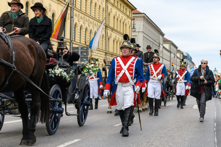 MUNICH, BAVARIA, GERMANY -  MARCH 11, 2018: couple in a horse waggon guarded by soldiers in old British uniforms at the St. Patricks Day Parade. Editöryel