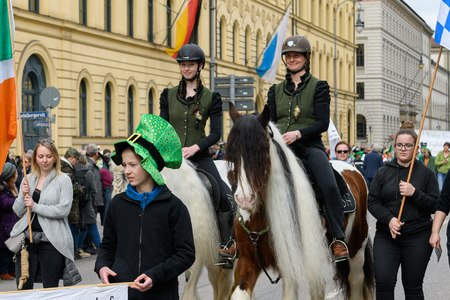 MUNICH, BAVARIA, GERMANY -  MARCH 11, 2018: group of people with horses representing the Schrankenscheiderhof at the St. Patricks Day Parade. Editöryel