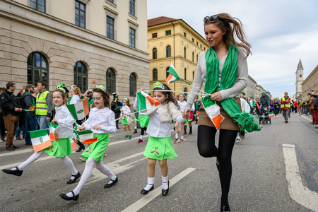 MUNICH, BAVARIA, GERMANY -  MARCH 11, 2018: group of girls representing the kerrygold company at the St. Patricks Day Parade. Editöryel