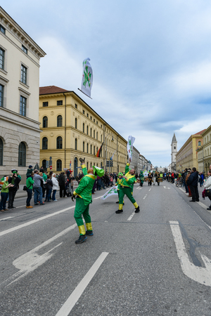 MUNICH, BAVARIA, GERMANY -  MARCH 11, 2018: group of flag wavers masked with red beard and green hat at the St. Patricks Day Parade.