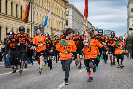 MUNICH, BAVARIA, GERMANY -  MARCH 11, 2018: close up on running kids in American football clothes  representing the Munich Rangers at the St. Patricks Day Parade.