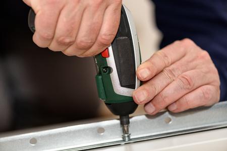 Schließen Sie oben auf Tischlerhänden mit dem kabellosen Schraubendreher, der Holzmöbel zusammenbaut. Handwerker DIY Konstruktion zu Hause. Standard-Bild