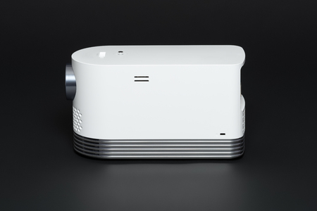 Stylish mini home cinema LED projector, lightweight tech gadget, front view.