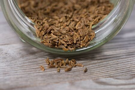 Close up on dried caraway seeds poured from glass on wooden cutting board. Stok Fotoğraf - 146950984