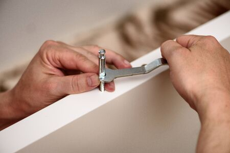 Handyman DIY construction at home: close up on hands with wrench assembling furniture.