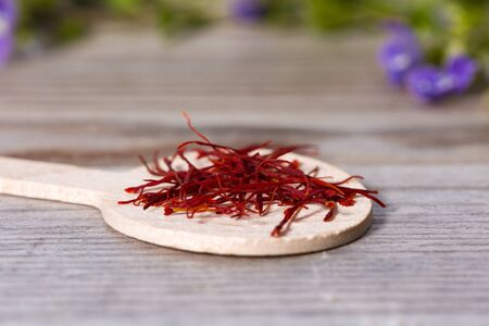 Close up on spoon with red saffron on wooden cutting board.