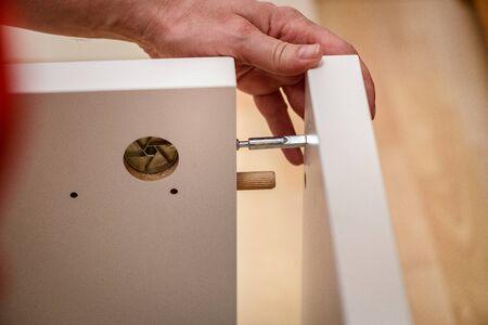 Close up on carpenter hands assembling wooden furniture. Handyman DIY construction at home.