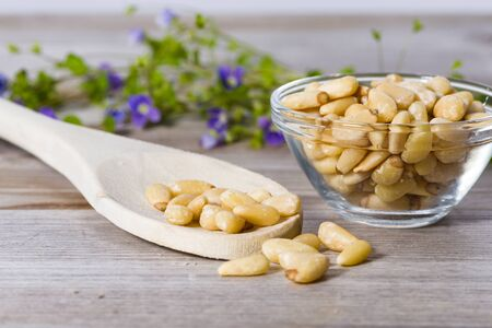 Group of pine nuts with spoon in cooking environment. Standard-Bild