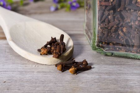 Group of dried cloves poured with spoon on wooden cutting board. Standard-Bild
