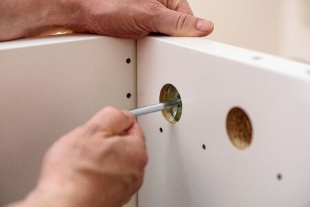 Handyman DIY construction at home: close up on hands with allen key assembling furniture.