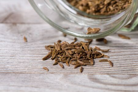Close up on dried caraway seeds poured from glass on wooden cutting board. Stok Fotoğraf - 148675328