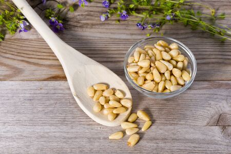 Group of pine nuts with spoon in cooking environment. Top down view. Standard-Bild