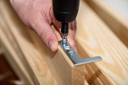 Close up on carpenter hands with cordless screwdriver assembling wooden furniture. Handyman DIY construction at home. Standard-Bild