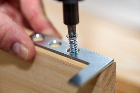 Close up on carpenter hands with cordless screwdriver assembling wooden furniture. Handyman DIY construction at home. Stok Fotoğraf