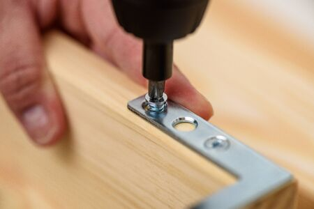 Close up on carpenter hands with cordless screwdriver assembling wooden furniture. Handyman DIY construction at home. Standard-Bild