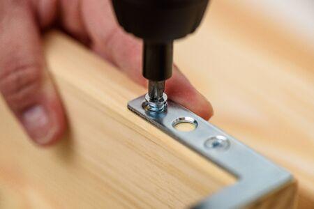 Close up on carpenter hands with cordless screwdriver assembling wooden furniture. Handyman DIY construction at home. Stok Fotoğraf - 146950804