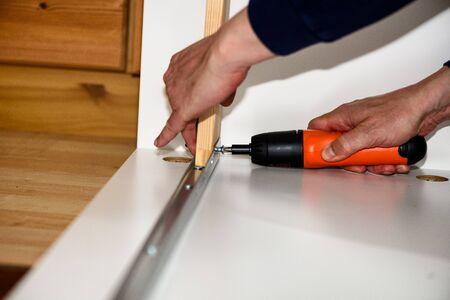 Close up on carpenter hands with cordless screwdriver assembling wooden furniture. Handyman DIY construction at home. Stok Fotoğraf - 148675339