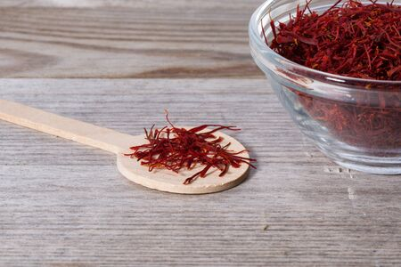 Close up on spoon with red saffron on wooden cutting board. Stok Fotoğraf - 148675340