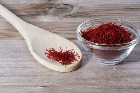 Close up on spoon with red saffron on wooden cutting board. Stok Fotoğraf - 148675342