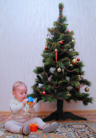 baby sit near Christmas tree photo