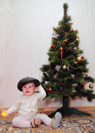 baby in peakes cap near Christmas tree photo